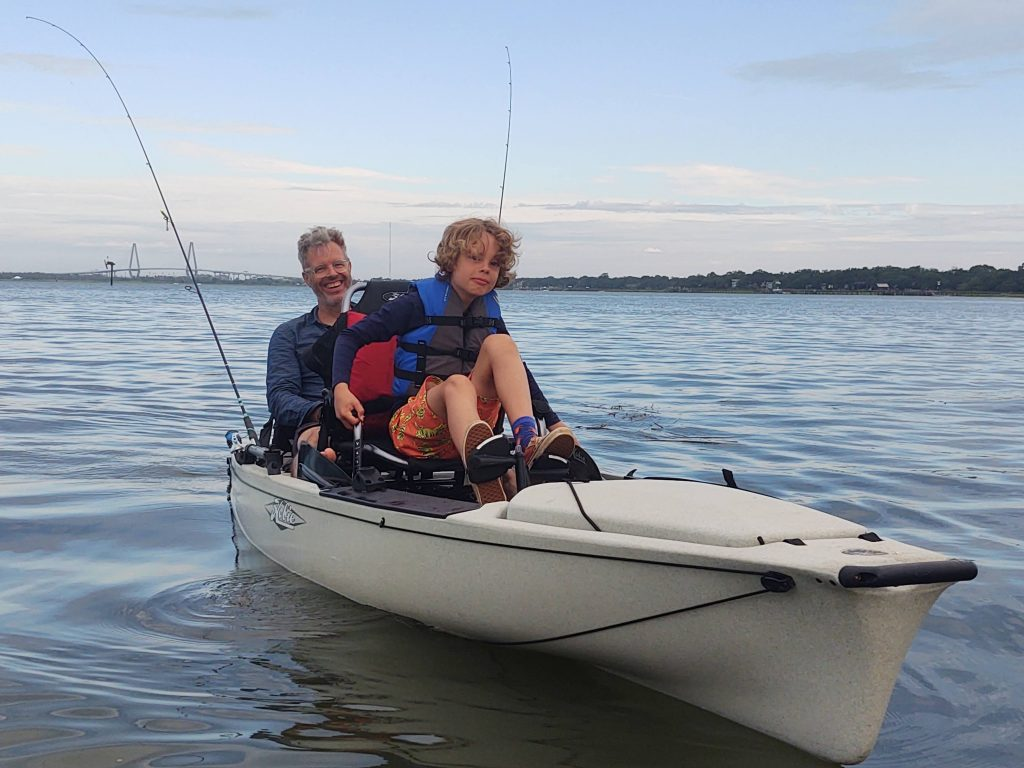 Father and son fishing in kayak