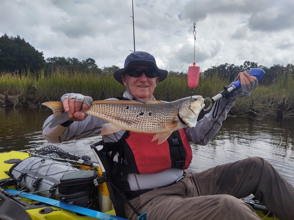 Kayak angler with redfish