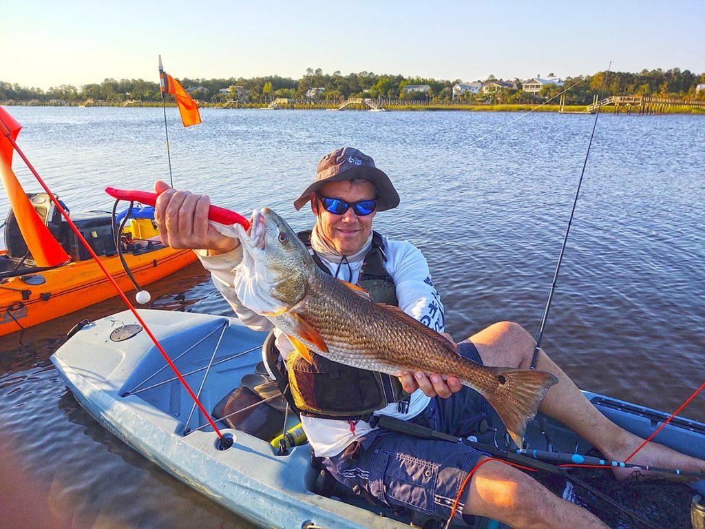 Kayak angler holding redfish